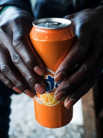 Italy, Calabria, Rosano. 2015. A young boy from Senegal drinks a beverage orange-flavored.