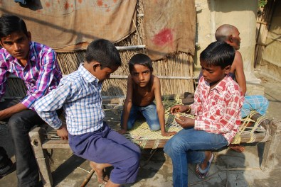Children play with paper cards depicting Hindu Gods as the research assistants finish their survey inside.
