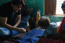 Atul smiles as a child reaches for the cloth covering the toy. In the 'A not B' test, a child's cognitive control is tested when they're asked to find an object hidden in front of them just moments before.