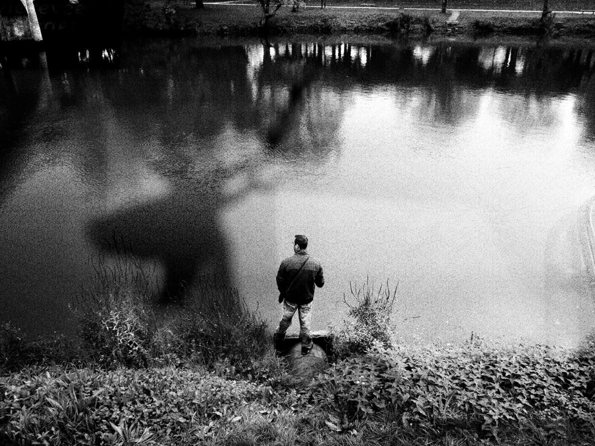 Un homme pêche et un cerf passe.