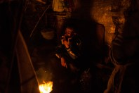 Mohamed, the Law student from Meknes, smokes a cigarrette near the fire on a cold night