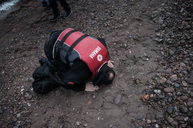 A man prays and kisses the ground on the shore after arriving with other refugees and migrants on the Greek island of Lesbos after crossing the Aegean sea from Turkey on October 21, 2015. An EU scheme to relocate asylum seekers from overstretched Italy and Greece could grind to a halt just two weeks after it began if member states fail to meet their obligations, an EU source said on October 21.