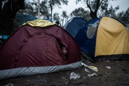 A migrant takes shelter from the heavy rain inside his tent, outside the Moria registration camp, on October 23, 2015, on the Lesbos island. Over 400,000 people have landed on Greek islands from neighbouring Turkey since the beginning of the year, most of them fleeing the civil war in Syria.