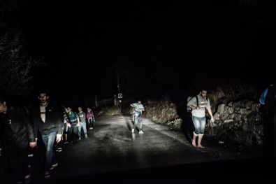 A group of new arrived refugees and migrants walking an uphill in direction to Mitilini harbour in Lesbos island, Greece