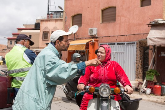 A woman asks for directions from a man on the roadside.