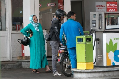 A woman waiting at a gas station.