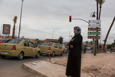 A woman waiting on the street corner in a busy intersection in Marrakech.