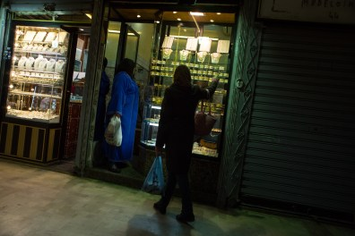 The jewel's light attracts the attention of two women at the window of one of the many shops.