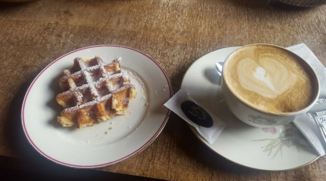Waffle with powdered sugar and coffee from KaffeeKlatsch in Davos. One of my favorite things to eat. I miss them. [Photo: Nicole Lamberson]