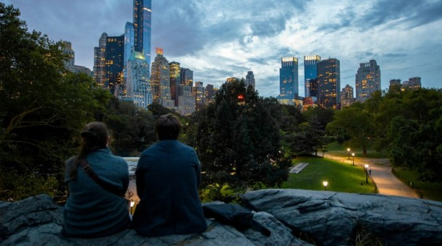 Two people sitting on rocks overlooking Central Park at dusk - Disappointing Destination
