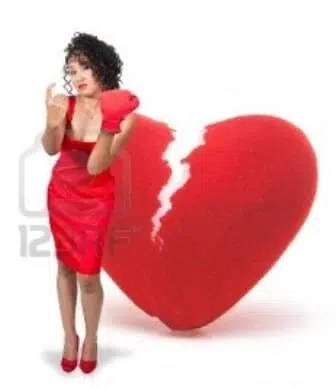 10857437-a-beautiful-black-woman-in-a-red-dress-wearing-a-boxing-glove-in-front-of-a-broken-heart