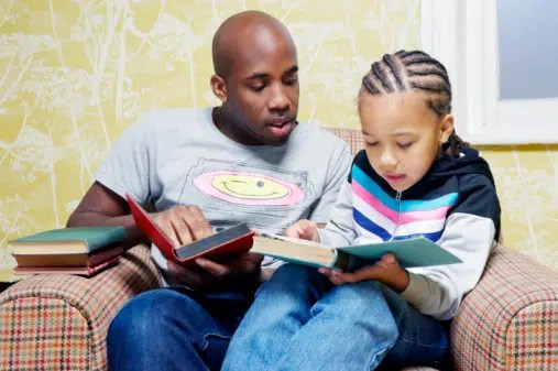father and son reading books on chair. image from https://ioneelev8.files.wordpress.com/2012/11/black-father-and-son-reading.jpg