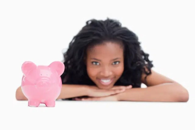 A smiling girl resting her head on her hands with a piggy bank in front of her. image from http://www.kiplinger.com/fronts/archive/basics/