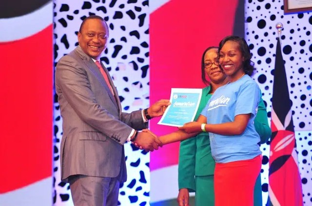 : President Uhuru Kenyatta presents completion certificate to a Generation Kenya graduate during the 4th Graduation ceremony at the KICC .Looking on is Cecily Kariuki, Cabinet secretary Ministry of Public Service, Youth & Gender Affairs. Photo - Courtesy