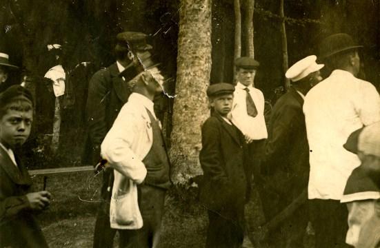 Tilskuere, bundtmagerJ.M. Mathiesen, Middelfart, i hvid jakke tv for træstamme