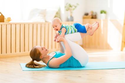 Maman qui fait du sport et du yoga avec bébé à la maison