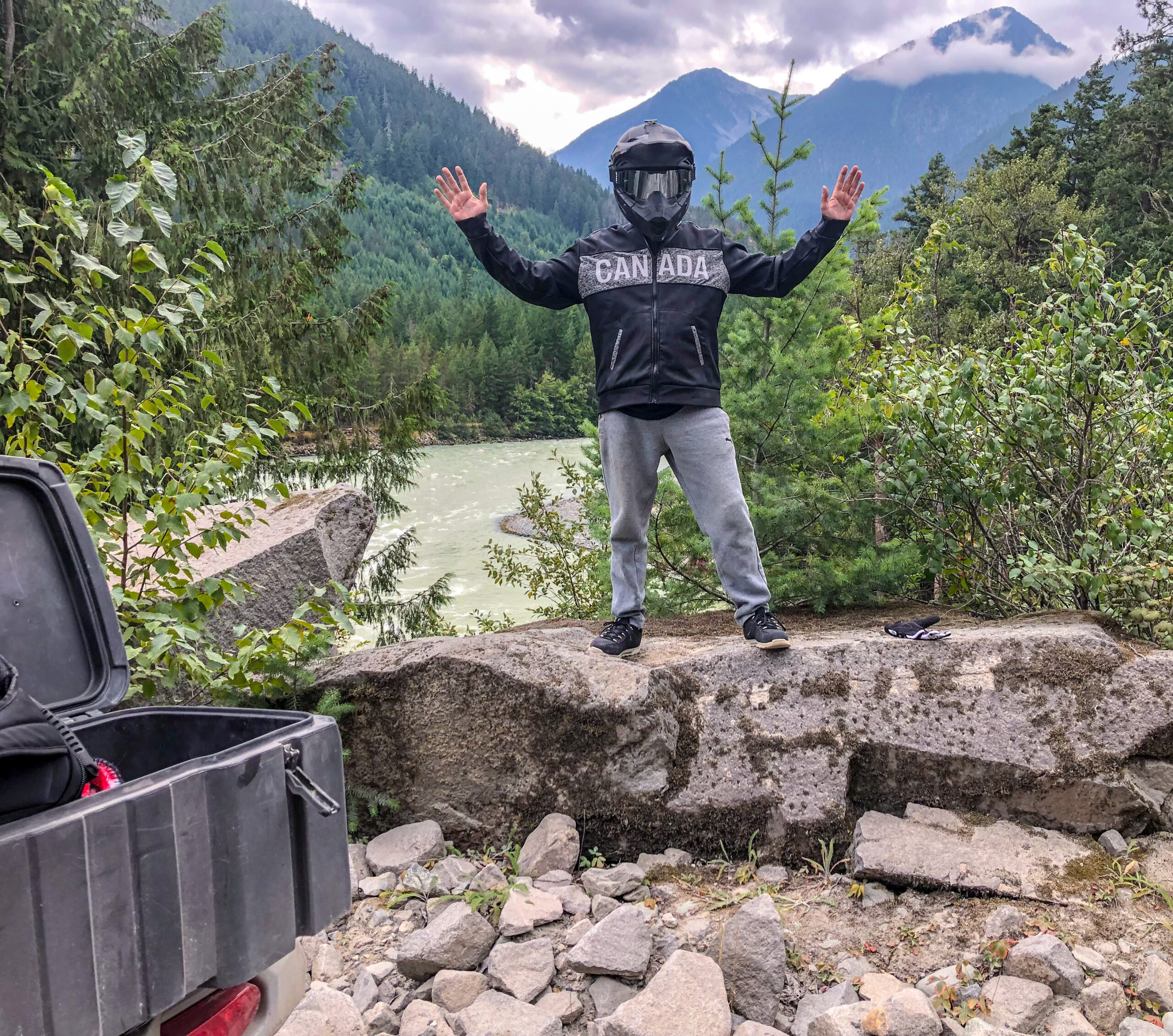husband standing on rocks with helmet on, river view behind ATV