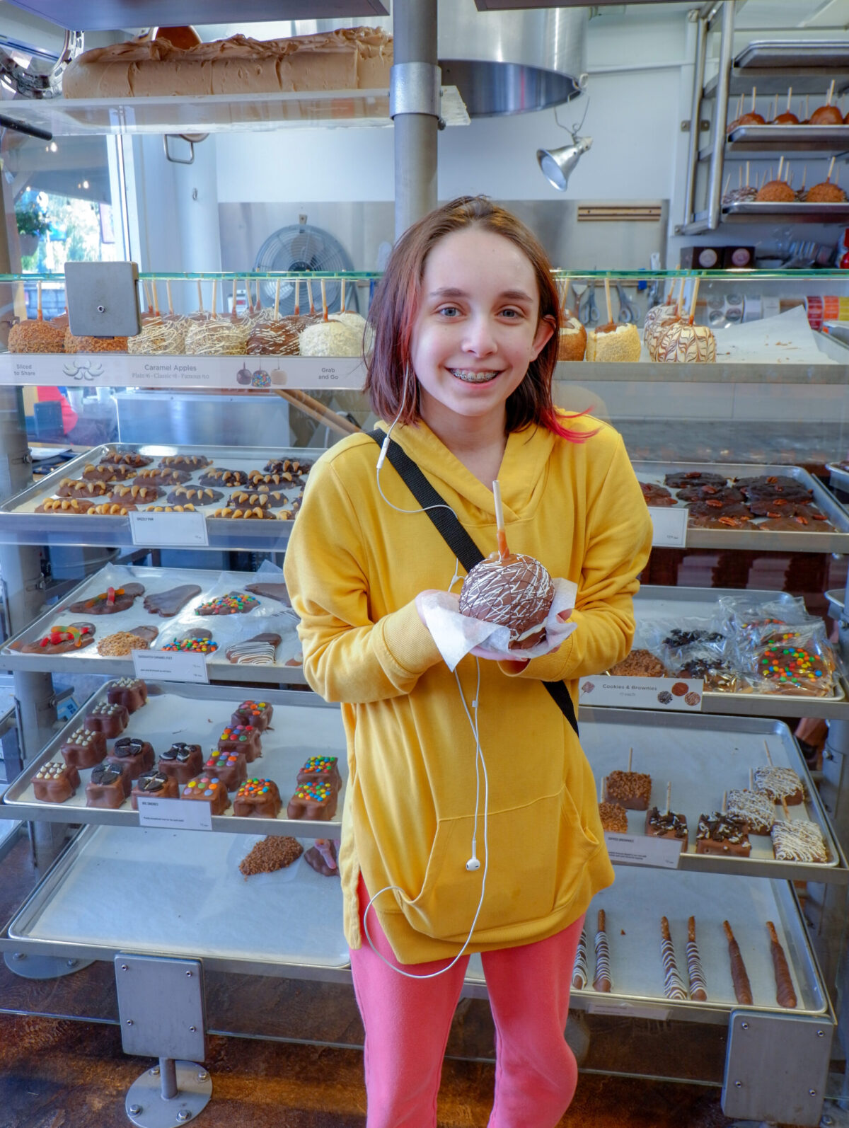 daughter holding candied chocolate apple at Rocky Mountain chocolate