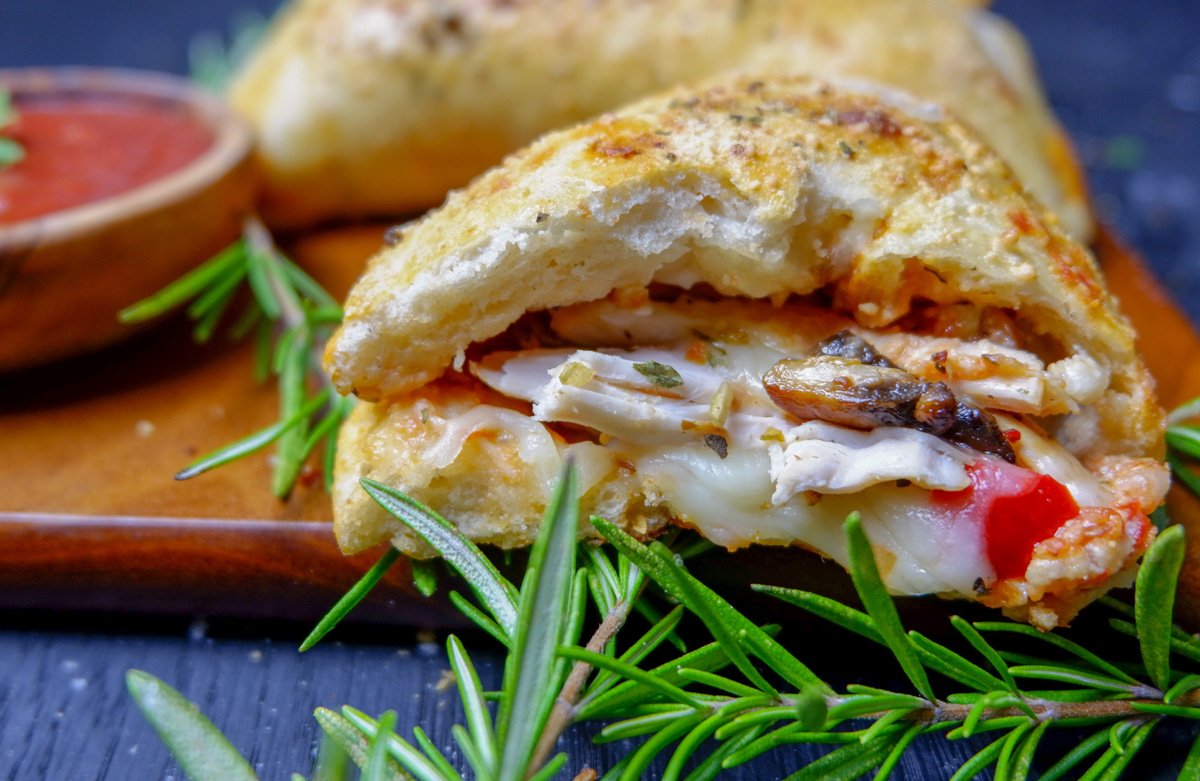 chicken calzone in half with chicken and melted cheese