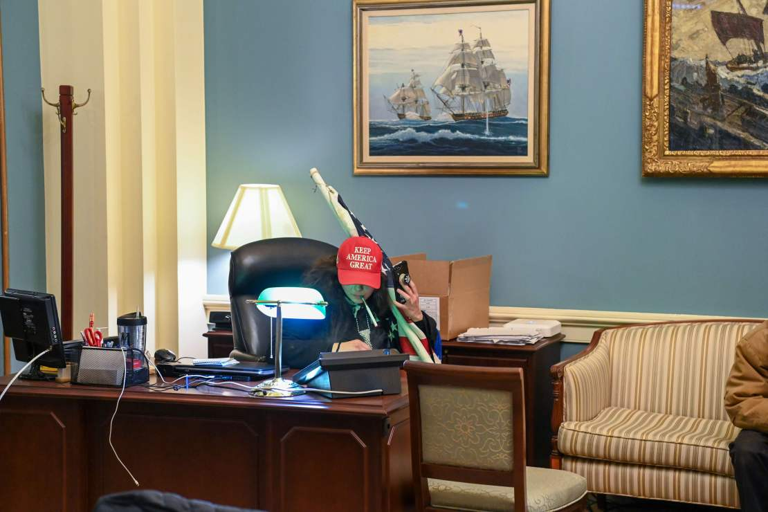 A supporter of US President Donald Trump sits at a desk after invading the Capitol Building.