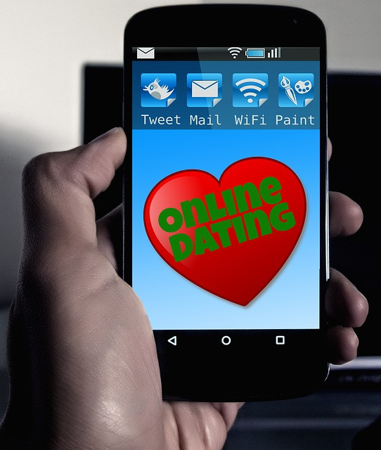 A hand holding phone with online dating written on the screen
