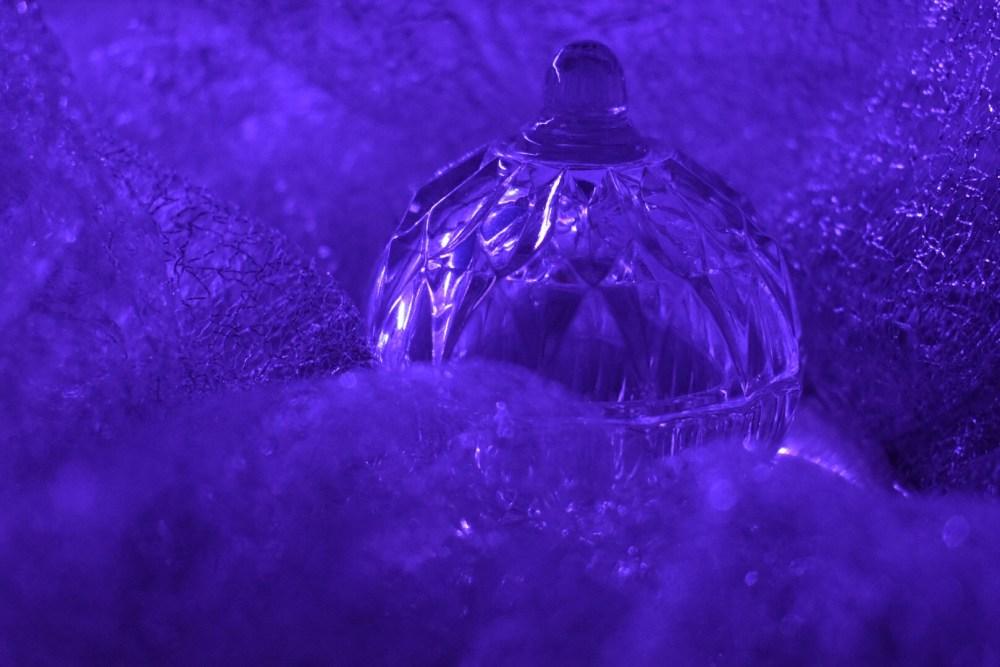 Glasgefäß, angestrahlt von lilafarbenen Licht