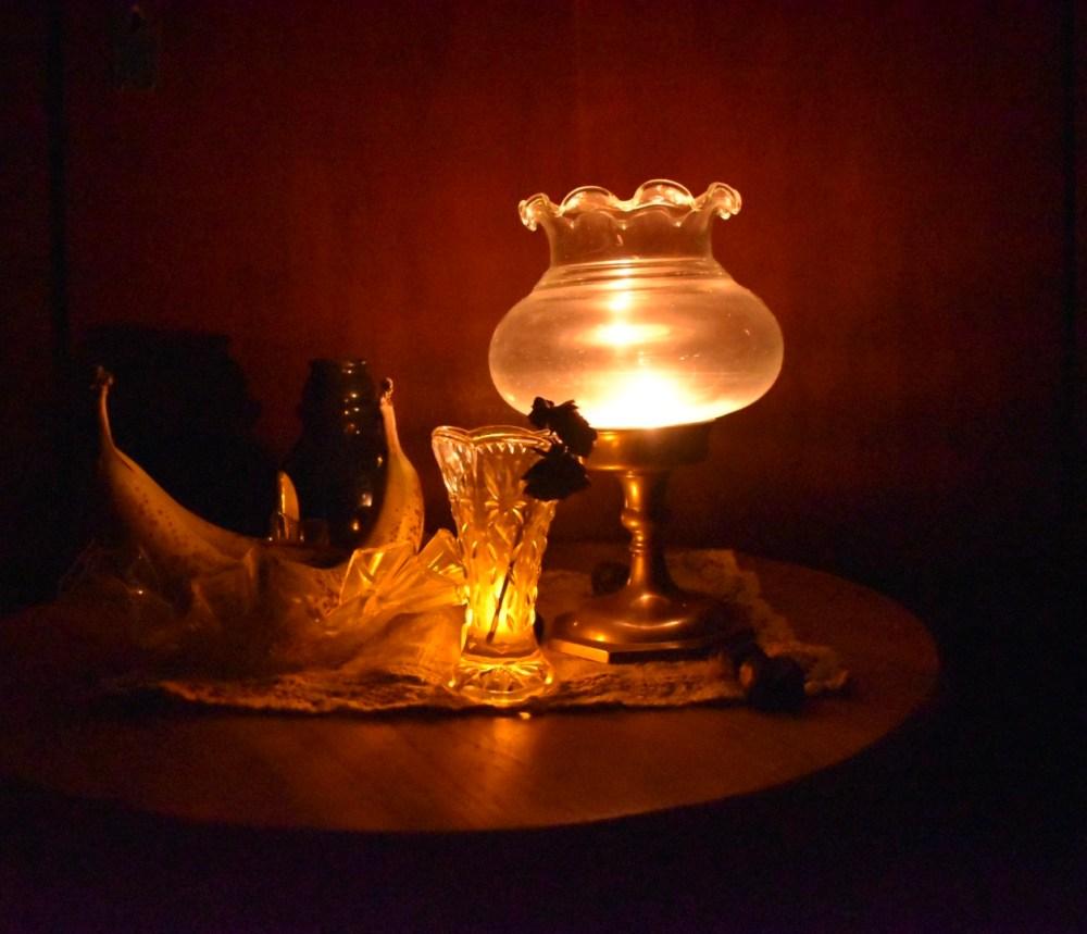 Stillleben mit Bananen, Kerzenleuchtern, Kastanien, verwelkten Rosen und Kerzenlicht