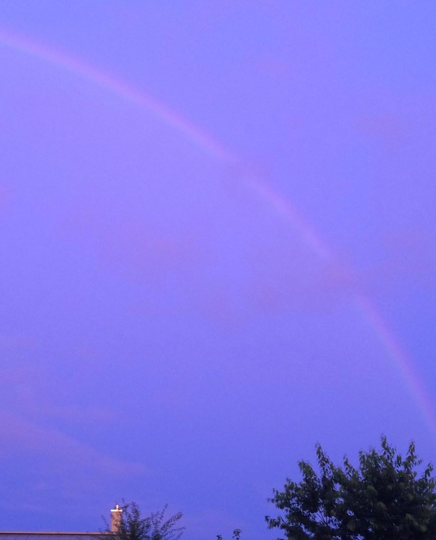Blasser Regenbogen bei ungewöhnlichem Sonnenuntergang