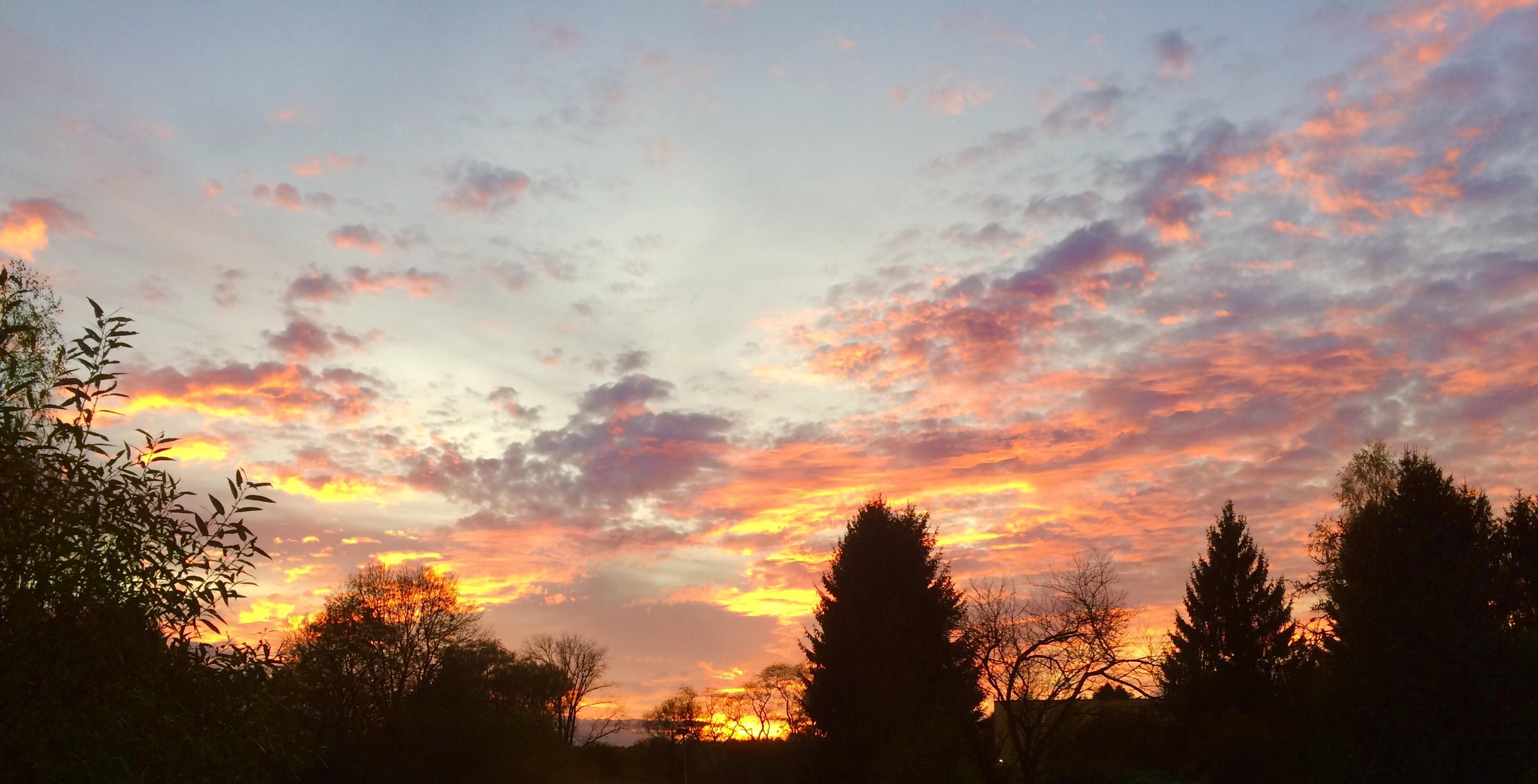Bunte Wolken, die von der untergehenden Sonne gefärbt werden