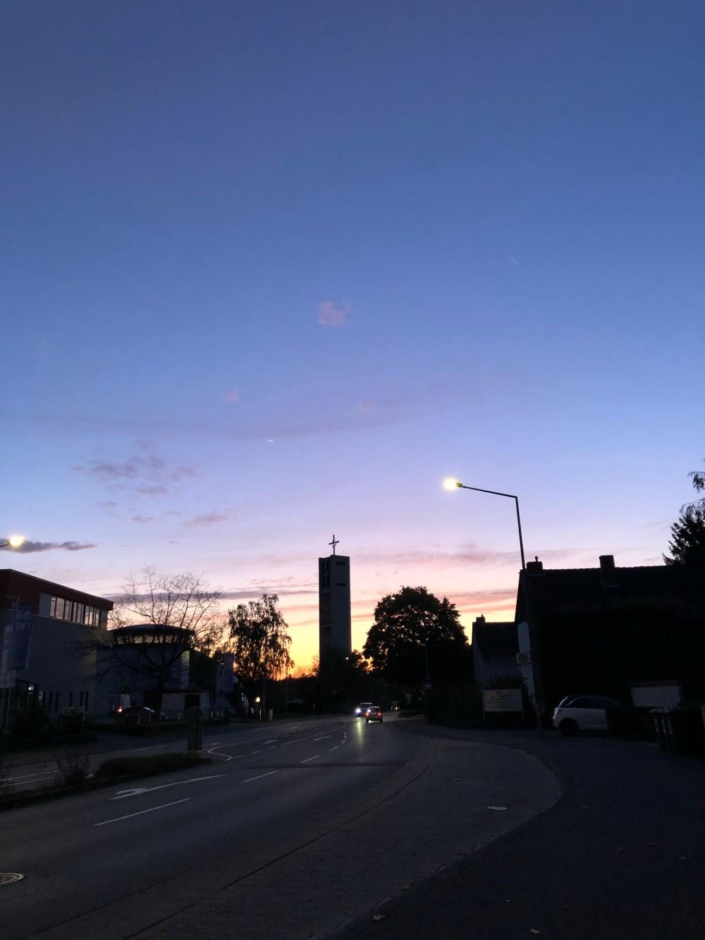 Straße zu einem Kirchturm mit Sonnenuntergang im Hintergrund
