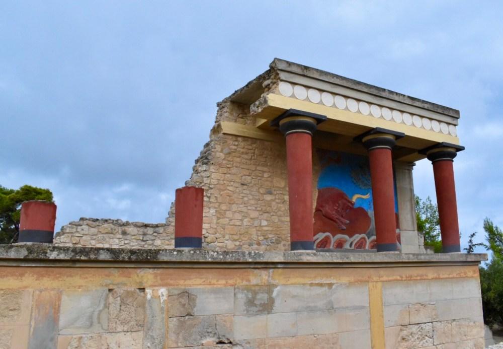 Fünf rote Säulen vor einem Fresko mit rotem Stier