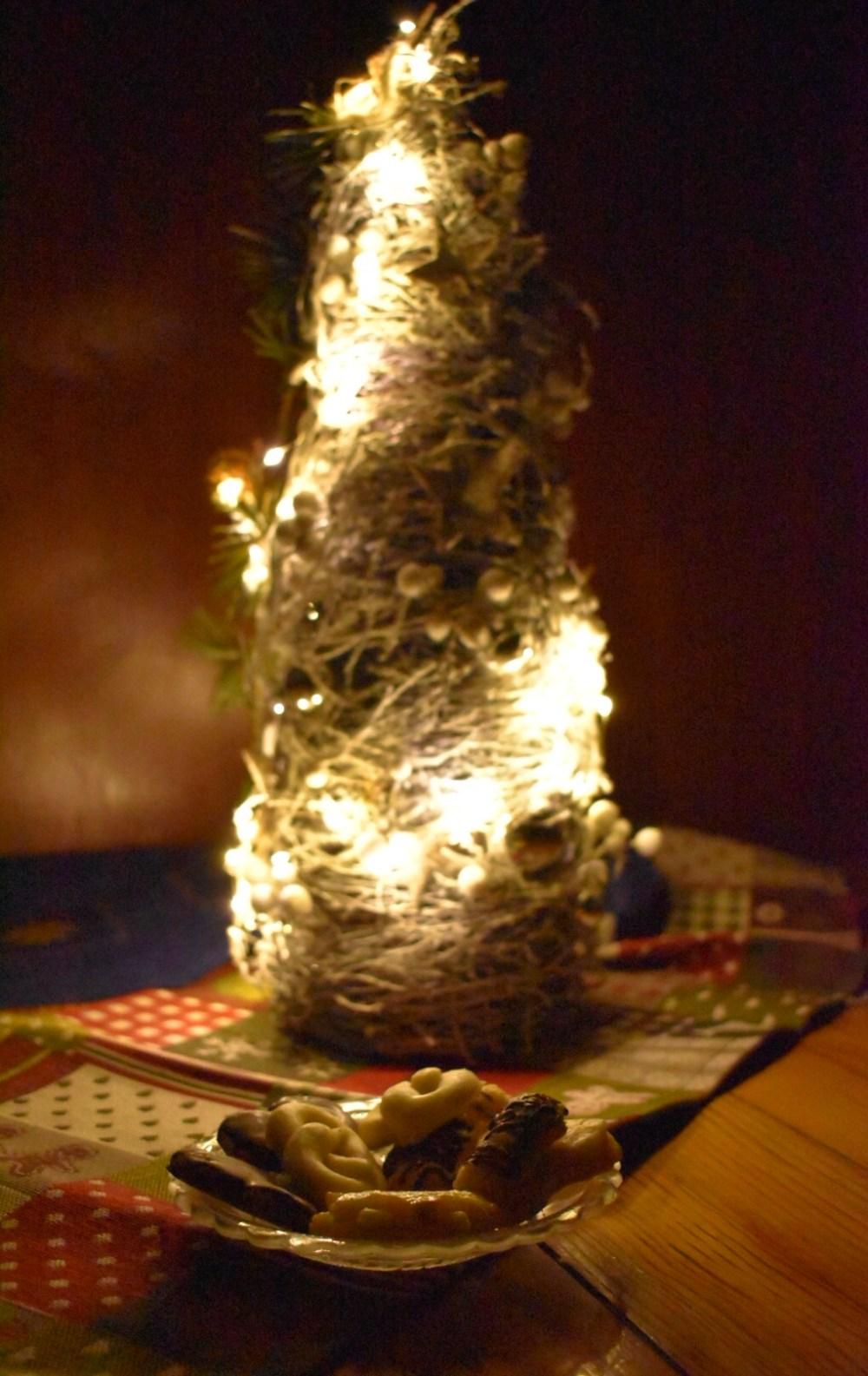 Stillleben mit beleuchtetem Weihnachtsbaum, Weihnachtsplätzchen und Tischdecken