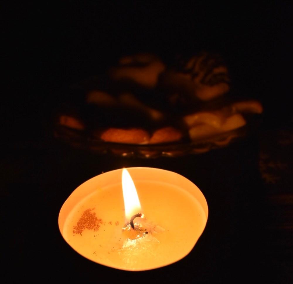 Brennende Kerze vor einem Teller mit Plätzchen