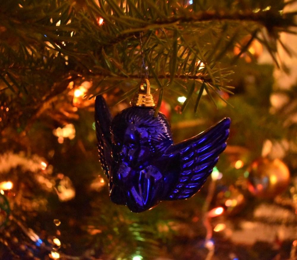 Blauer Engel im beleuchteten Tannenbaum