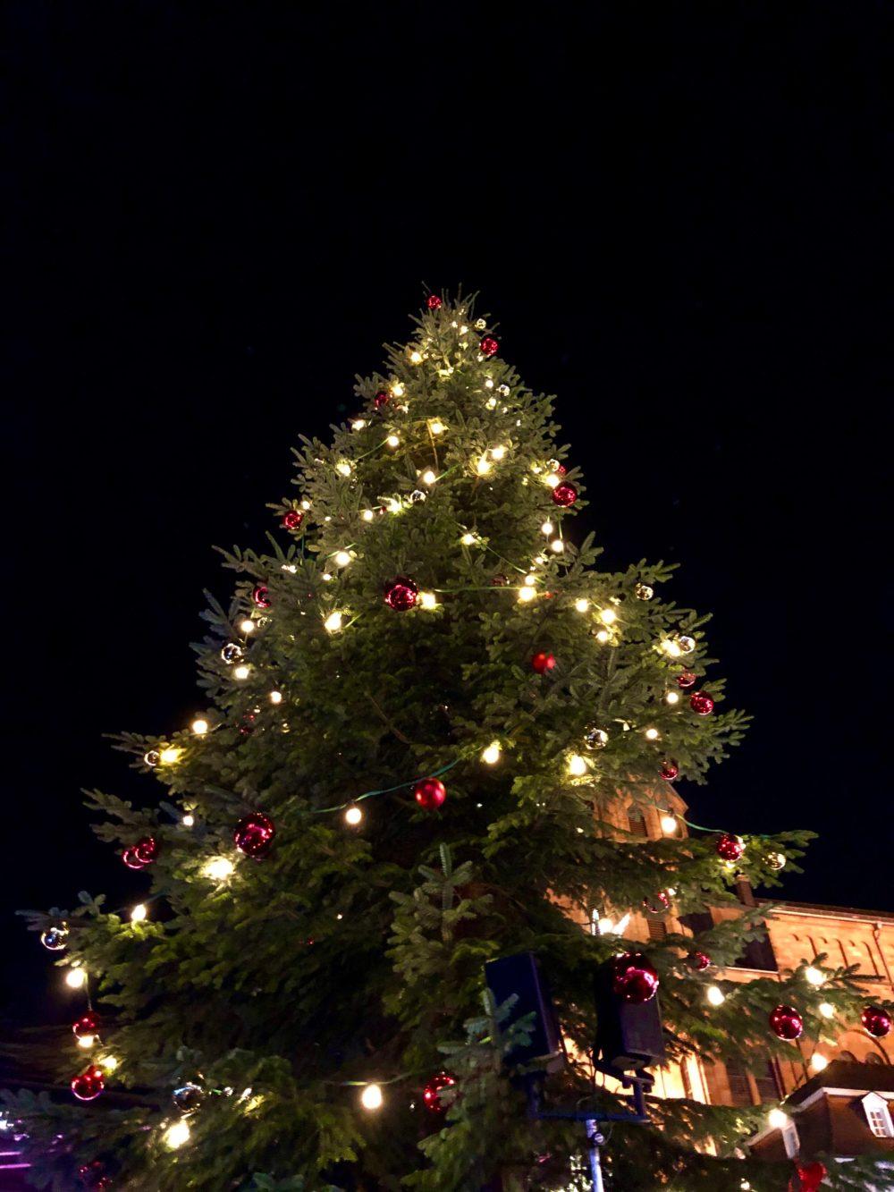 Beleuchteter Weihnachtsbaum mit roten Kugeln auf einem Weihnachtsmarkt