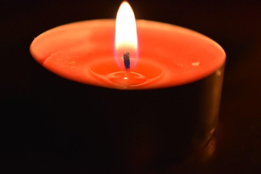 Orangene brennende Kerze im Dunklen