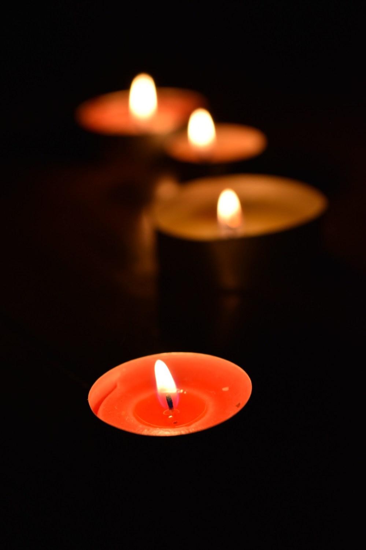 Orangene Kerze im Kerzenlicht mit drei anderen Kerzen