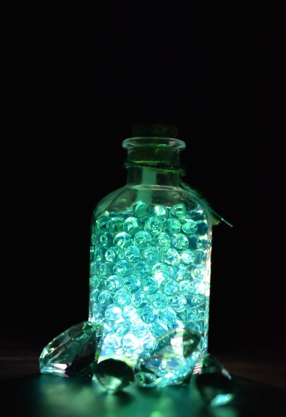 Strahlende Glasflasche mit Kugeln und Diamanten im Dunklen