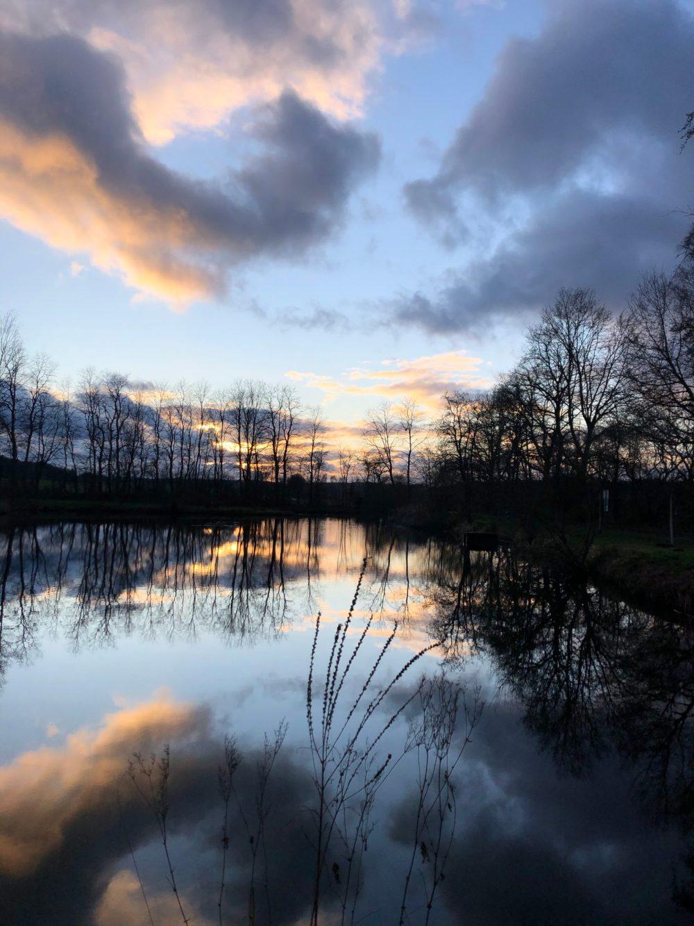 Von der untergehenden Sonne gefärbte Wolken über einem Gewässer