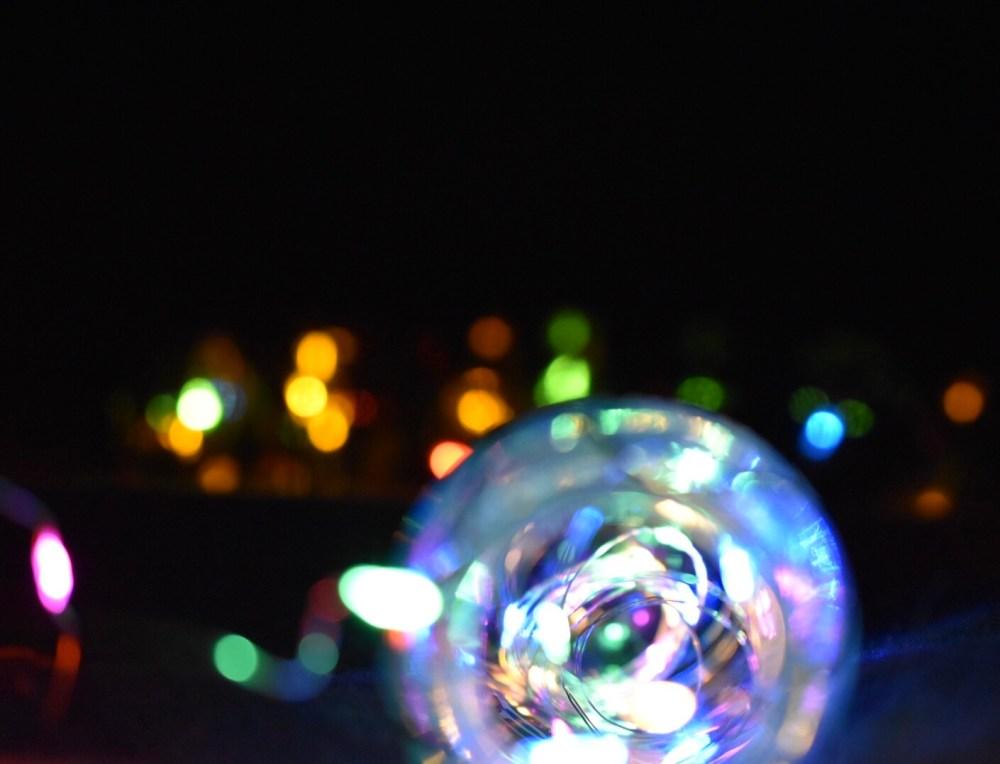 Farbenfroh beleuchtete Flaschen mit bunten Lichtpunkten im Hintergrund