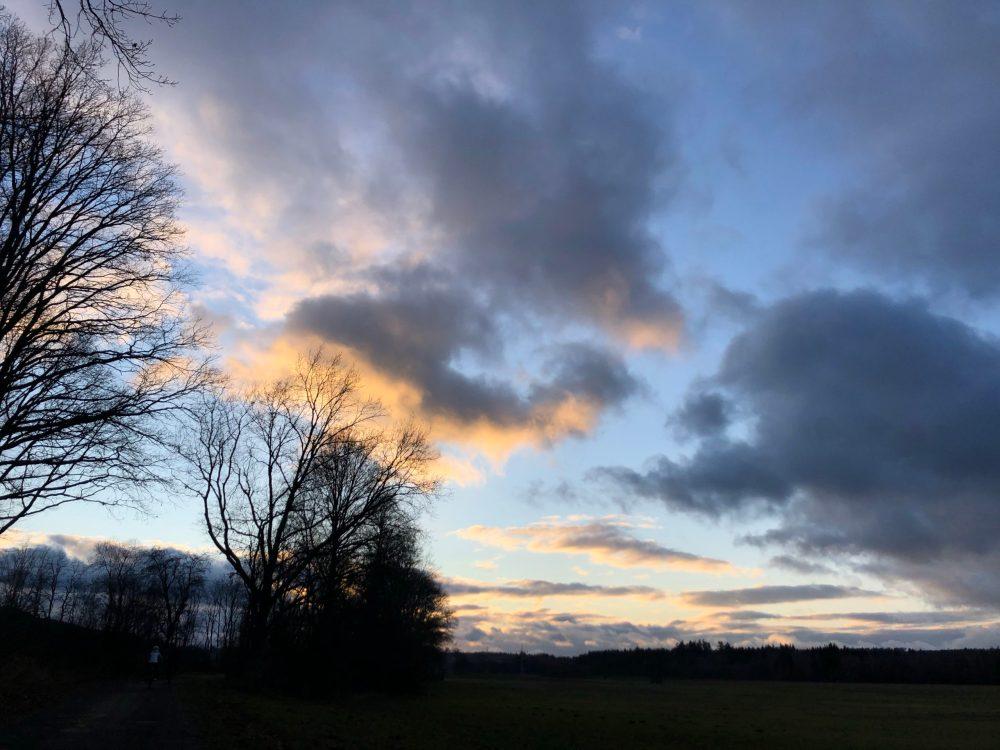 Von der Sonne untergehenden Sonne beleuchtete Wolken über einem Geld