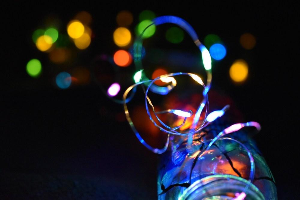 Aus einer einer Flasche herausragende Lichterkette im Dunkeln