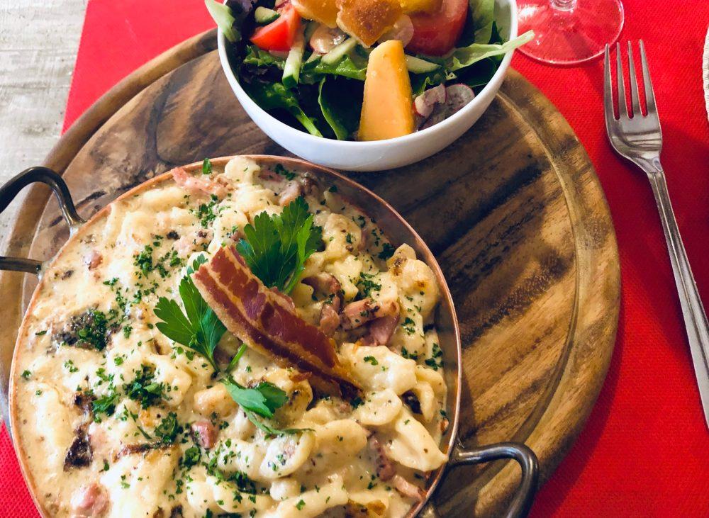 Käsespätzle und Salat auf einem Holzbrett auf einer roten Tischdecke
