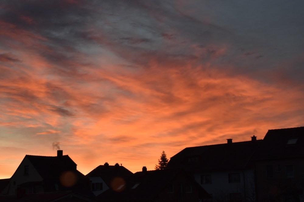 Silhouetten der Häuser unter dem orange strahlendem Himmel während eines Sonnenaufgangs