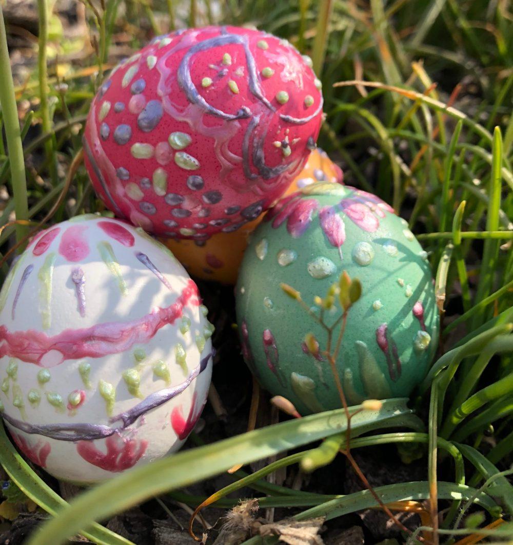 Vier gestapelte Ostereier im Grass