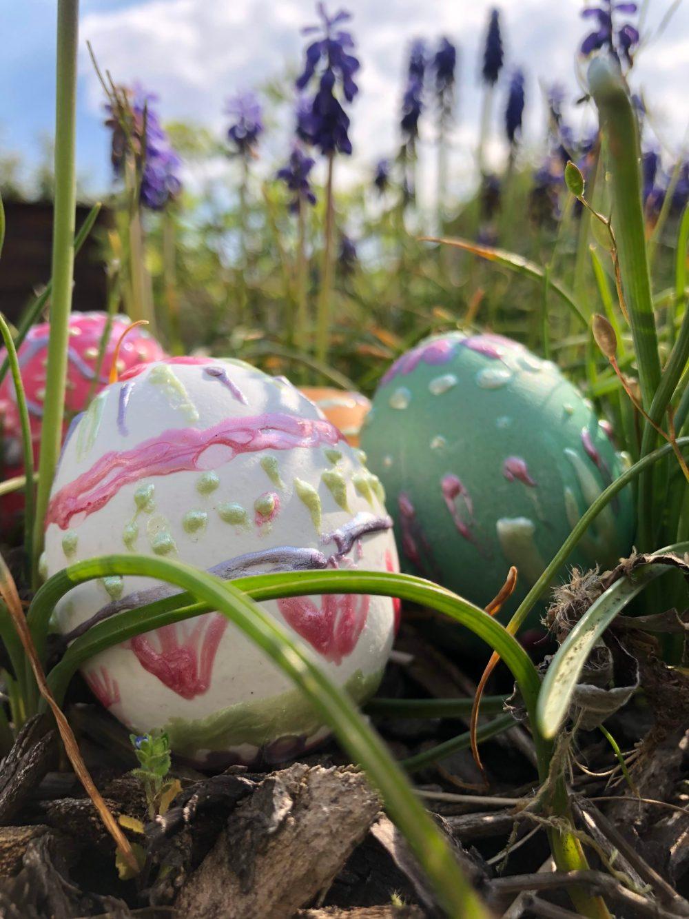 Frühlingshafte Ostereier im Grass mit Traupenhyazinthen im Hintergrund