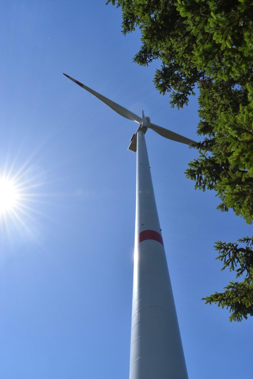 Windrad vor strahlend blauem Himmel mit Sonne von unten fotografiert