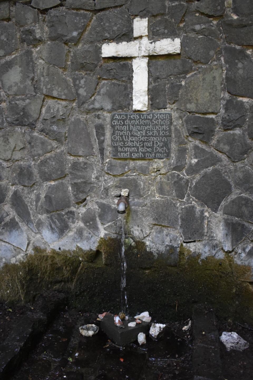 Kreuz mit Gedicht über einer Wasserquelle