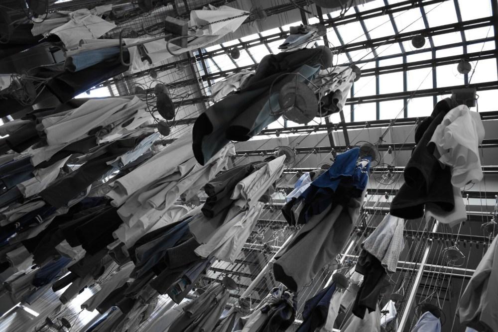 Aufgehängte Arbeitskleidung in schwarz weiß mit blauer Farbe fotografiert