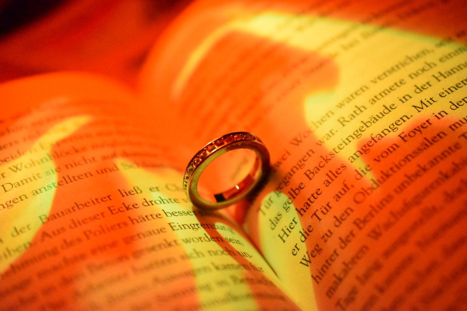 Ring wirft ein Herzschatten auf ein Buch im feurigen Licht